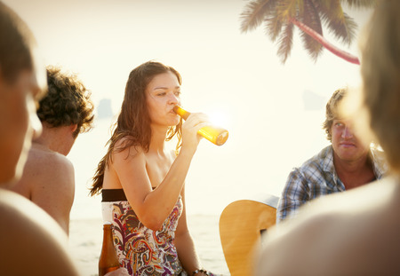 Beautiful Casual Woman Drinking Beer on a Beach photo