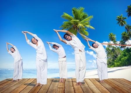 Group of People Doing Yoga on Beach photo