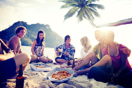 personas festejando: Grupo de jóvenes alegres que se relaja en una playa
