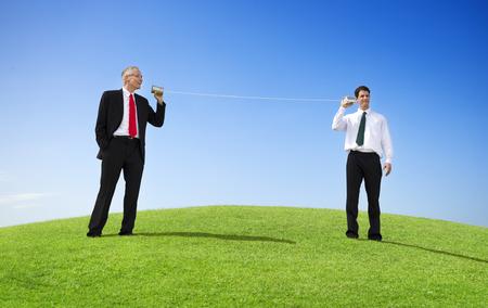 Business Men Outdoors Talking Through Tin Can Phone photo