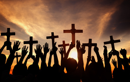 Group of People Holding Cross and Praying in Back Lit photo