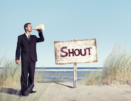 inductive: Businessman Holding loudspeaker with Signboard on Beach