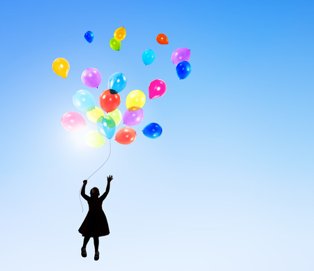 Little Girl in the Air Holding Balloons photo
