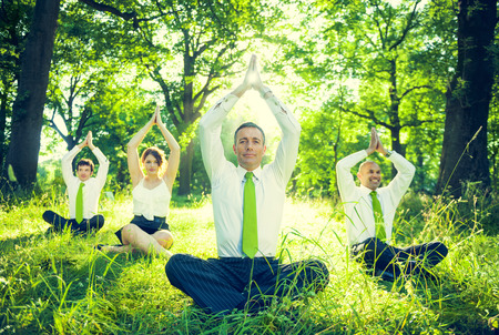 Group of business people dong yoga in the forest