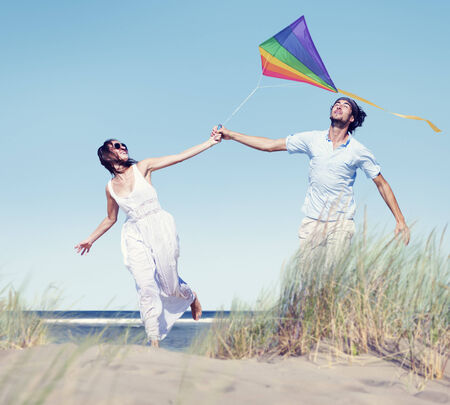 flying man: Cheerful Couple Playing Kite by the Beach