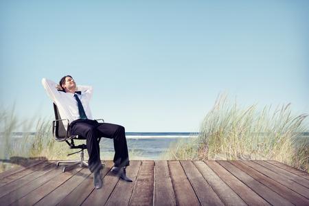 Zakenman ontspannen op bureaustoel op het strand Stockfoto