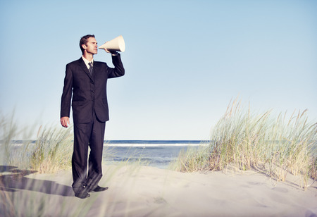 inductive: Business Man Holding loudspeaker on Beach Stock Photo
