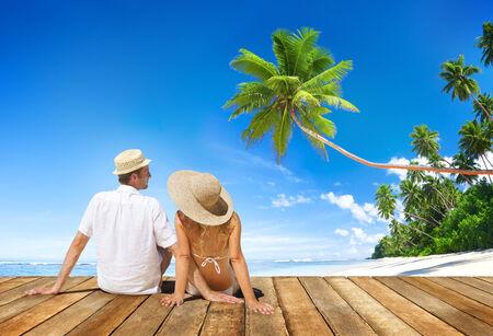 Couple Sitting on Wooden Floor at Beach