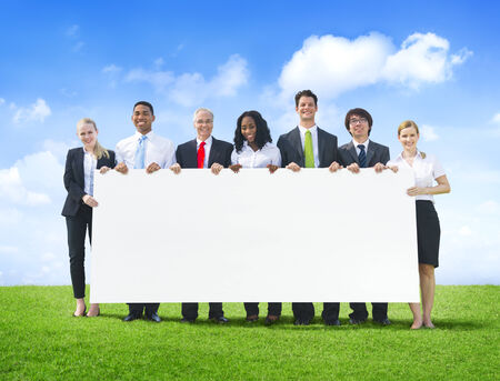 Cheerful Business People Holding Empty Billboard Outdoors photo