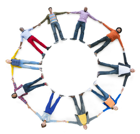 Diverse People Laying Down while Holding Hands Stock Photo