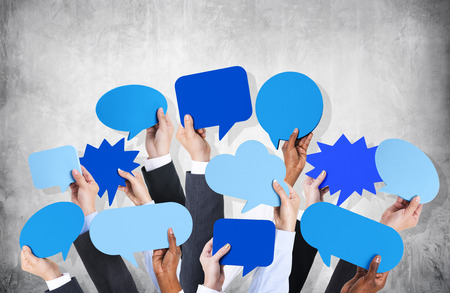 Business arms raised with speech bubble by concrete wall  photo