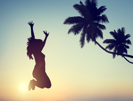 winning woman: Silhouette of a Young Woman Jumping with Excitement Stock Photo
