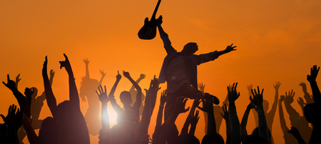 Young Man Performing with a Guitar in Front of the Crowd Imagens