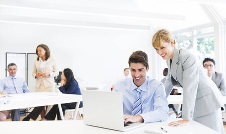 training consultant: A Boss Guiding her Employee in Front of the Laptop Stock Photo