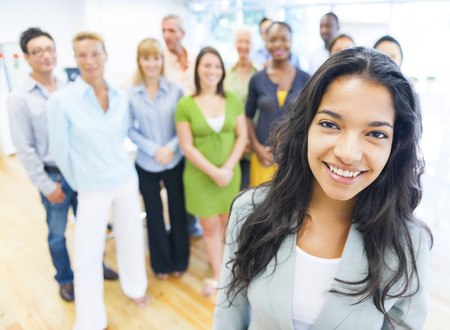 leadership training: Beautiful young woman with colleagues in the background Stock Photo