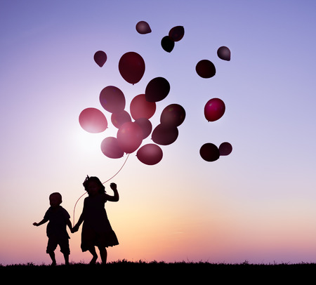 Children Outdoors Holding Balloons Together photo