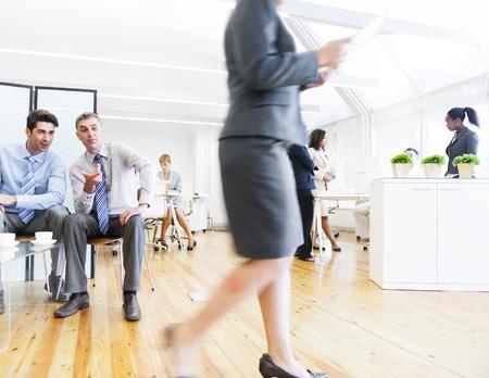 Twee corporate Mannen staren en roddelen over hun vrouwelijke collega