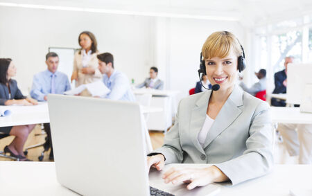 A Cheerful Telecommunications Agent in a Busy Office  Banco de Imagens