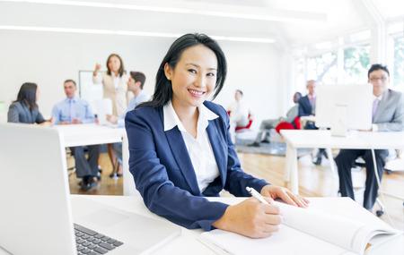 陽気な企業の女性彼女の事務処理を行う