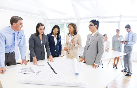 architect: Group of Multi Ethnic Architects Planning for a New Project with their Blueprint Stock Photo