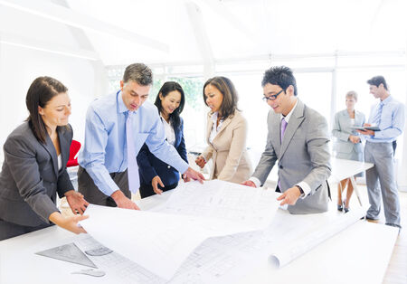 architect: Group of Architects Planning on a New Project with their Blueprint