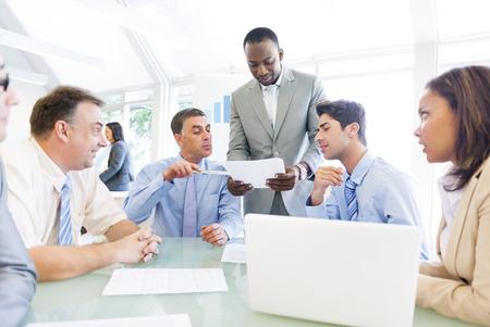 ビジネスマンの彼の同僚に彼の仕事のアイデアを示す