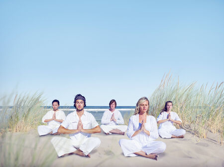 Group of People Doing Yoga on Beach photo