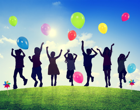Children Outdoors Playing Balloons Together Stock Photo