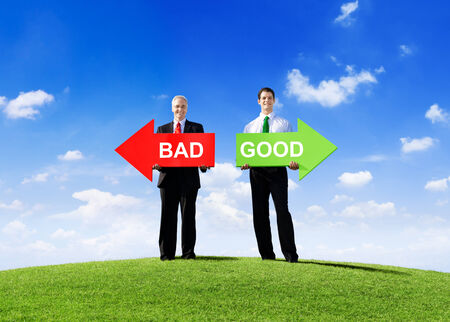Two Businessmen Holding Contrasting Arrows for Bad and Good photo