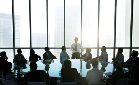 corporate buildings: The leader of the business people giving a speech in a conference room. Stock Photo