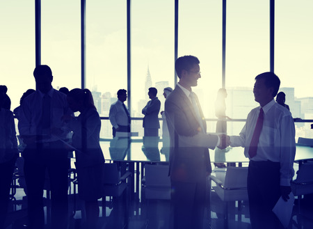ビジネス: ニューヨークのスカイラインの前に握手する人々 のグループ。