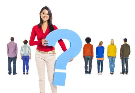 signo de interrogacion: Vista trasera de personas multi�tnicas y una joven mujer sosteniendo el signo de interrogaci�n