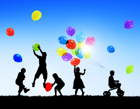 Silhouettes of Children Playing Balloons and Riding Bicycle photo
