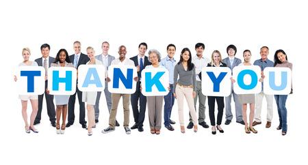 多民族グループの保持しているビジネス人々 のグループがプラカードありがとうを形成