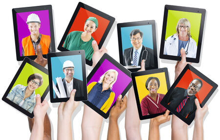 Group of Hands Holding Tablets with Peoples Faces photo