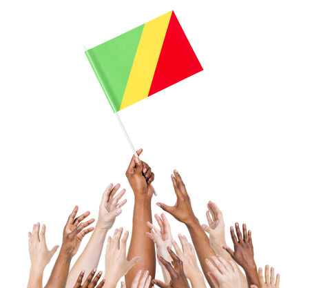 raise the white flag: Group of multi-ethnic people reaching for and holding the flag of Republic of the Congo. Stock Photo