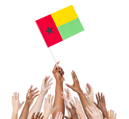 raise the white flag: Group of multi-ethnic people reaching for and holding the flag of Guinea Bissau. Stock Photo