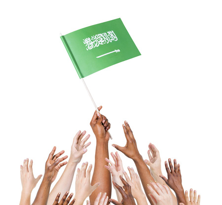 raise the white flag: Group of multi-ethnic people reaching for and holding the flag of Saudi Arabia. Stock Photo
