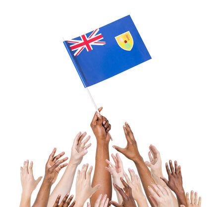 winning location: Human hand holding Turks and Caicos Islands flag among multi-ethnic group of peoples hand