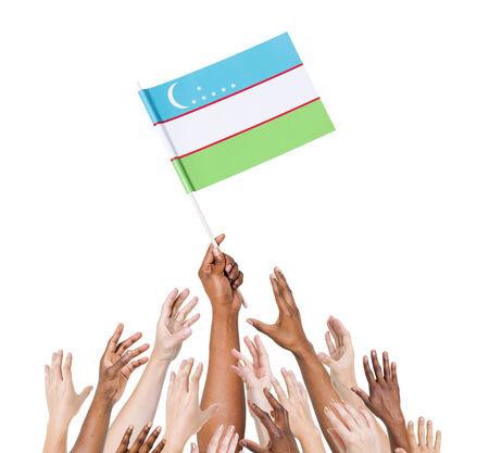 winning location: Human hand holding Uzbekistan flag among multi-ethnic group of peoples hand Stock Photo