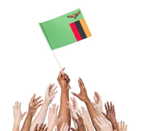 zambian: Human hand holding Zanbia Flag among multi-ethnic group of peoples hand
