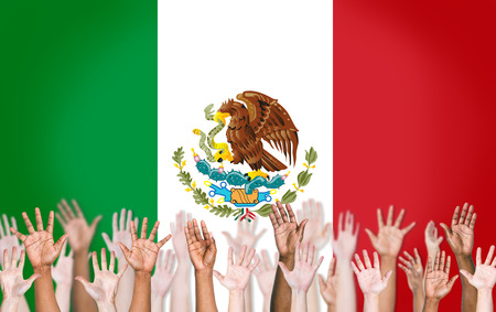 bandera mexicana: Grupo de armas Multi�tnico elevada y una bandera de M�xico como fondo Foto de archivo