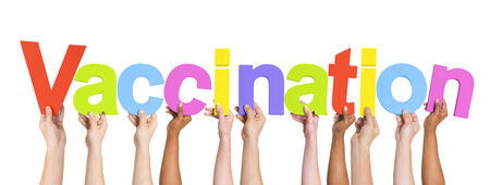 flu vaccinations: Multiethnic Arms Raised Holding Text Vaccination Stock Photo