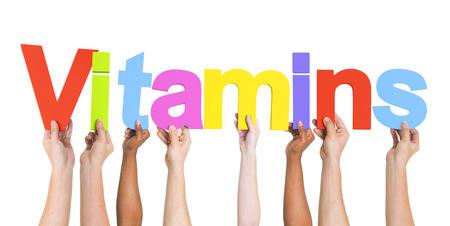 Diverse Hands Holding The Word Vitamins Foto de archivo