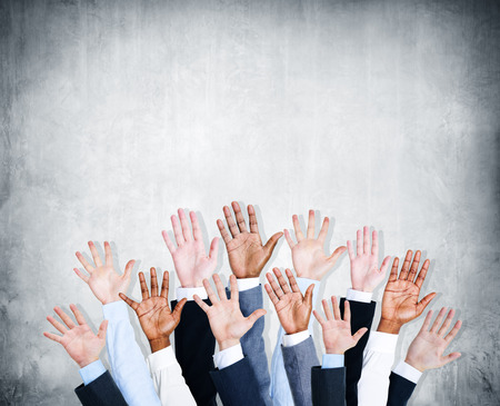 Group of human arms raised with concrete wall. photo