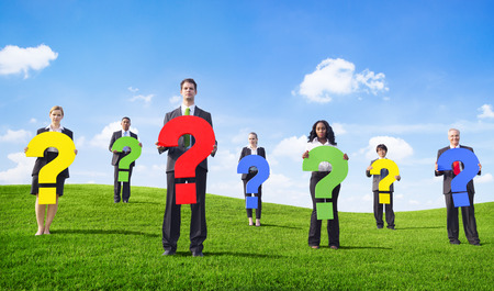 Angry Business People Outdoors Holding Question Marks photo