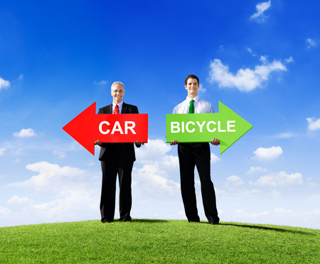 Two Businessmen Holding Contrasting Arrows for Car and Bicycle photo