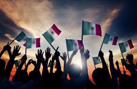 bandera mexicana: Grupo de personas que ondeaban banderas mexicanas en Contraluz