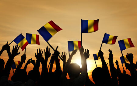 Group of People Waving Romanian Flags in Back Lit photo
