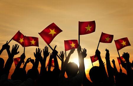 gente saludando: Grupo de personas que ondeaban banderas vietnamitas en Contraluz